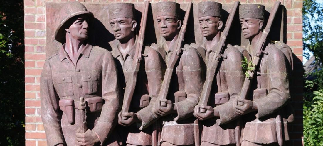 Das Foto zeigt die rechte Seite des Askari-Reliefs im Tansania-Park in Hamburg. Zu sehen ist auf dem Relief eindeutscher Offizier und vier bewaffnete Schwarze Soldaten in militärischer Uniform.
