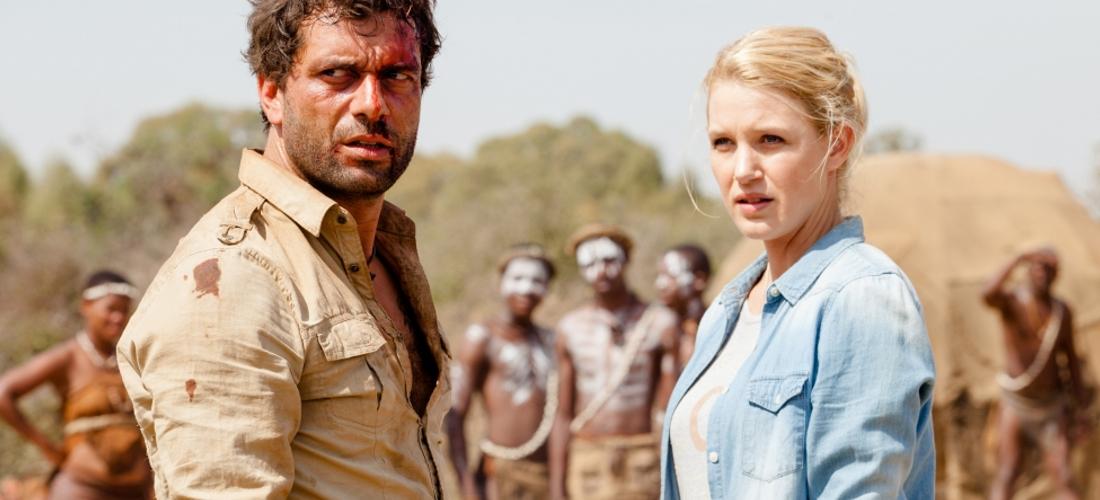 """Das Foto zeigt einen Screenshot aus der ZDF Mediathek aus dem Film """" Jana und der Buschpilot: Einsame Entscheidung"""". Abgebildet sind ein europäischer Mann und eine europäische Frau im Vordergrund und im Hintergrund mehrere bemalte Schwarze Menschen."""