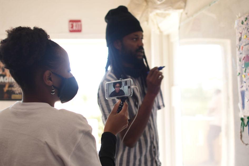 Die Künstler*innen Vitjitua Ndjiharine (l., mit Smartphone in der Hand) und Nashilongweshipwe Mushaandja im Gespräch vor einem Plakat, Namibia 2020. © Hildegard Titus