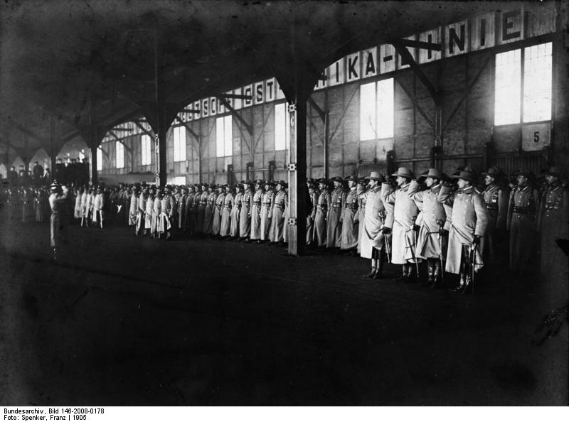 Die Schwarz-Weiß-Fotografie zeigt die Verabschiedung der Schutztruppe im Gebäude der Deutschen Ost-Afrika-Linie 1905. Zu sehen ist das innere einer Halle in der in Reihen aufgestellt uniformierte Männer zu sehen sind.