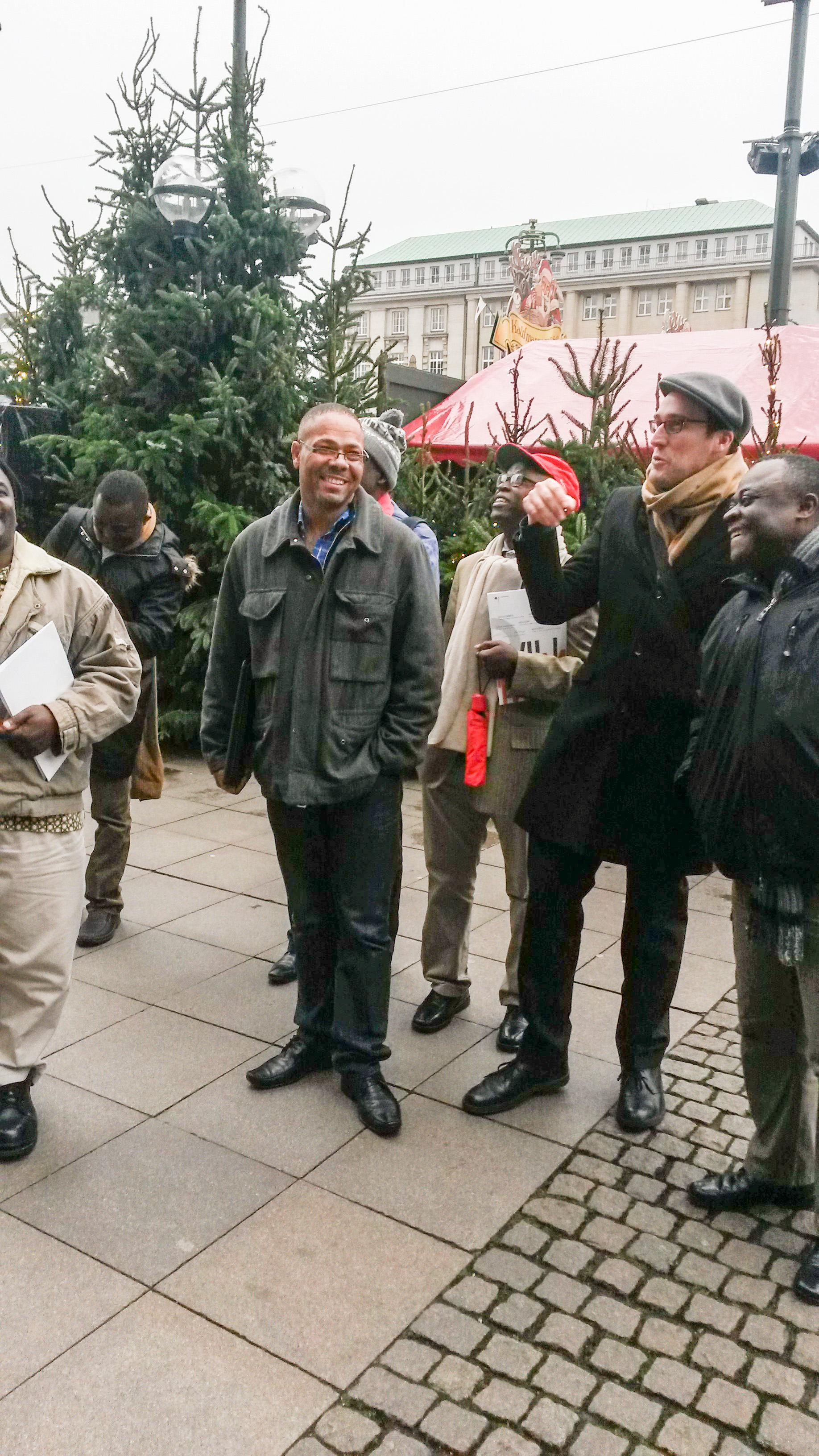 Das Foto zeigt die Stadtführung in Hamburg von Kim Todzi. Kim Todzi steht mit den Teilnehmern der Stadtführung auf dem Rathausmarkt.