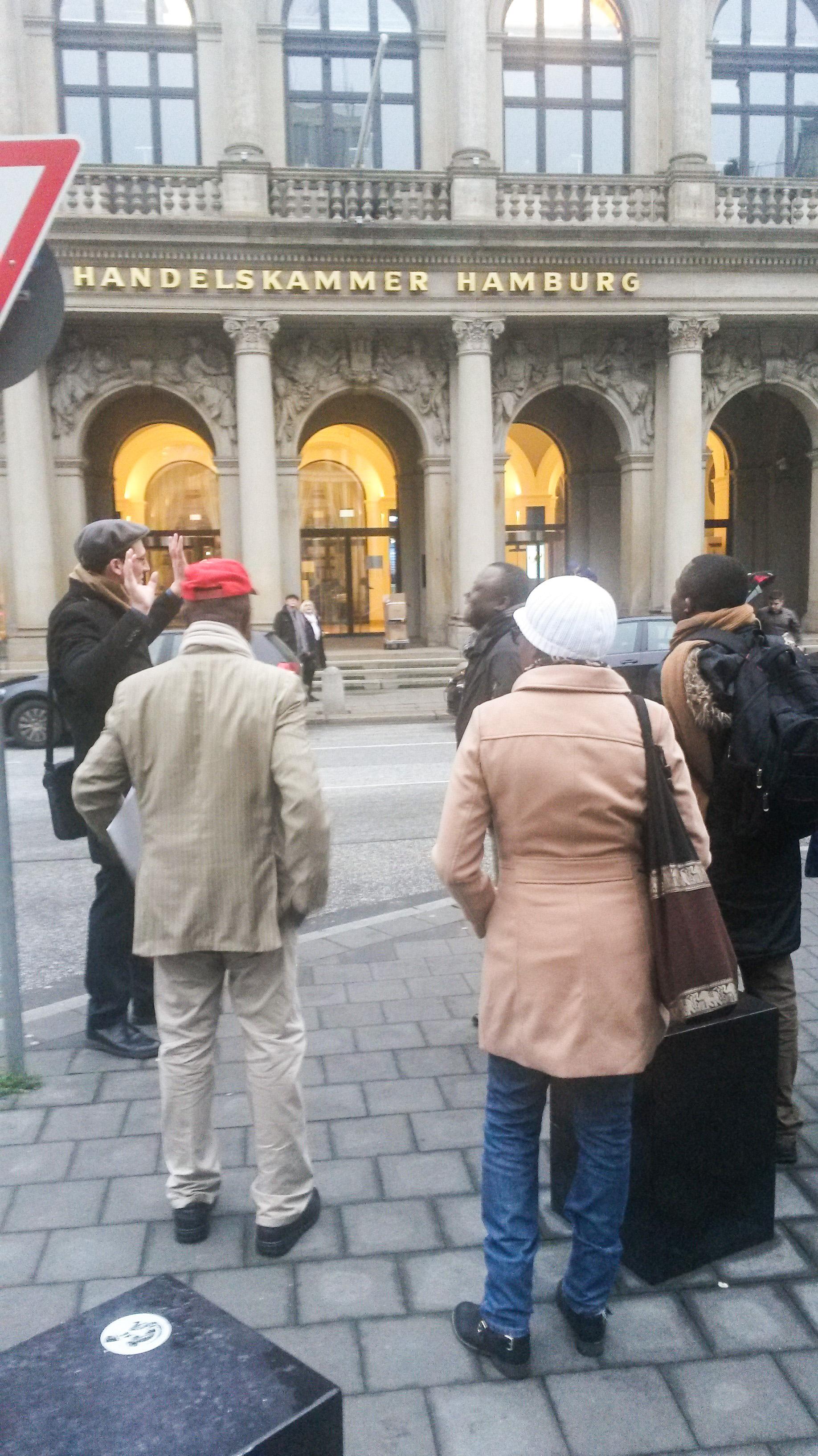 Das Foto zeigt die Stadtführung in Hamburg von Kim Todzi. Kim Todzi steht mit den Teilnehmern der Stadtführung vor der Handelskammer Hamburg.