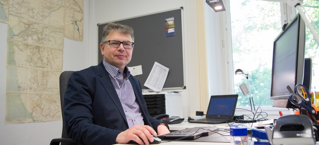 Das Foto zeigt Prof. Dr. Jürgen Zimmerer im Büro.