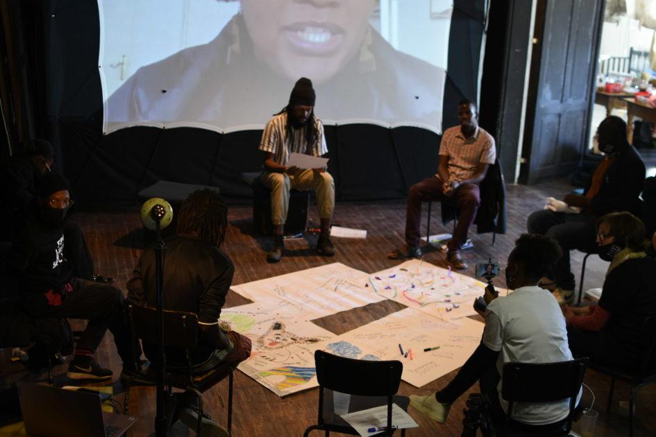 Mitwirkende eines Workshops im Rahmen des Projekts 'Ovizire • Somgu: From Where do We Speak?' in einer Diskussionsrunde, am Boden Plakate, im Hintergrund eine Leinwand. © Hildegard Titus