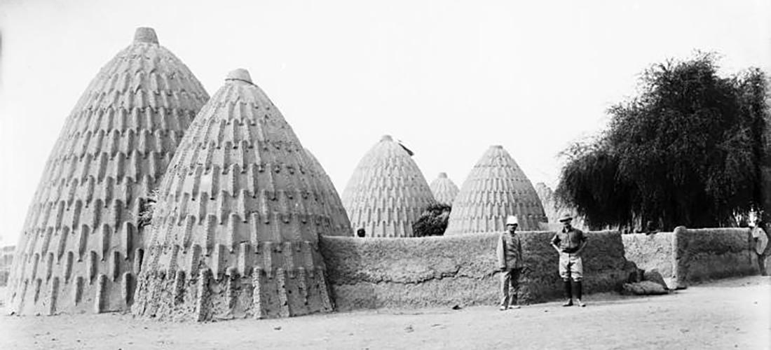 Die Schwarz-Weiß-Fotografie zeigt zwei Expeditionsmitglieder, die vor einem Hof der Musgum posieren. Die Häuser sind kegelförmig.