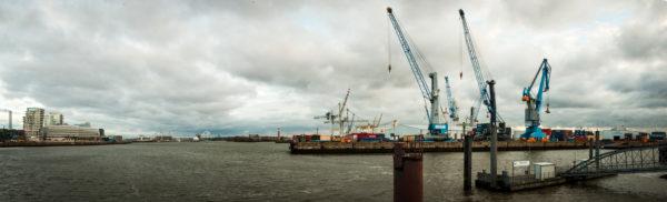 Das Foto zeigt den Hamburger Hafen mit dem Süd-West Terminal auf der rechten Bildseite. Zu sehen sind mehrere Kräne und Container auf dem Süd-West Terminal.