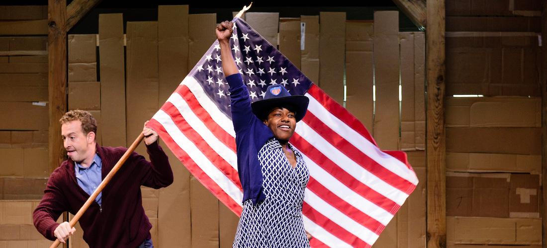 """Die Fotografie zeigt eine Szene aus dem Theaterstück """"Underground Railroad Game"""". Zu sehen ist vor einer Kulisse aus Pappe und Holz eine Schwarze Frau, die eine Faust in die Höhe hebt. Hinter ihr läuft ein Mann mit einer Flagge der USA."""