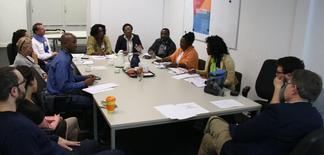 Die Fotografie zeigt eine Diskussionsrunde in den Räumen der Forschungsstelle. Die Teilnehmer der Diskussionsrunde sitzen zusammen an einer Tischgruppe.