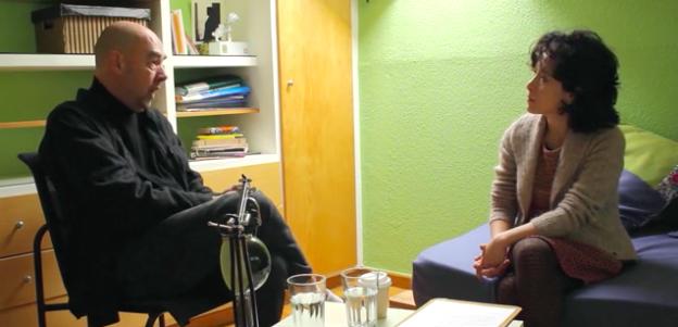 Das Foto zeigt einen Screenshot aus dem Interview zwischen Santiago Alba Rico und Tania Mancheno. Die beiden unterhalten sich, S. Alba Rico sitzt auf einem Stuhl und T. Mancheno auf einer Couch ihm gegenüber.