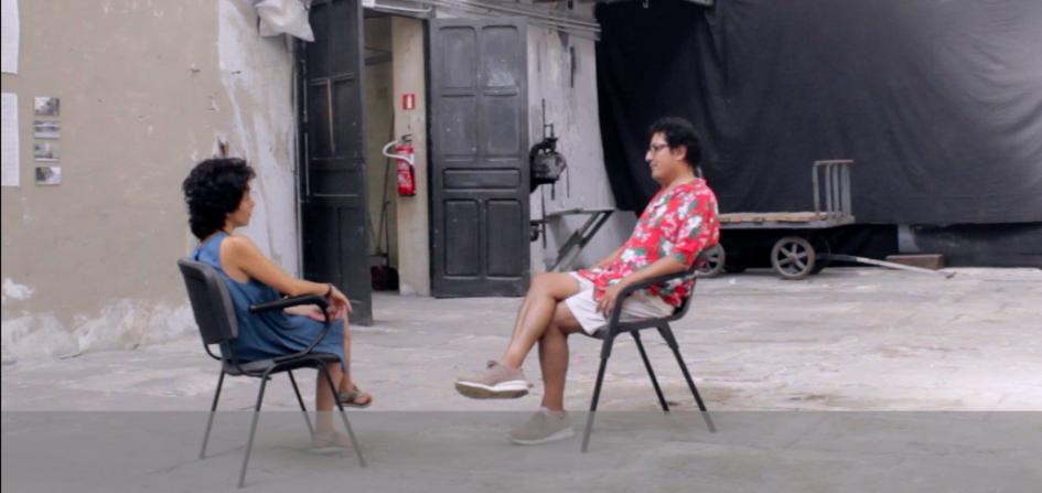 Das Foto zeigt einen Screenshot aus dem Interview zwischen Fabiano Kueva und Tania Mancheno. Die beiden sitzen sich in einer Halle auf zwei Stühlen gegenüber und unterhalten sich.