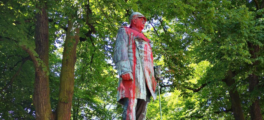 Das Foto zeigt das Bismarck-Denkmal mit roter Farbe angemalt. Bismarck wird in diesem Denkmal in preußischer Militärmacht dargestellt.