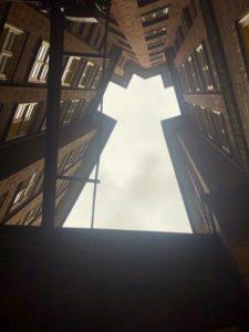 Das Foto zeigt den Blick vom Innenhof des Chilehauses zum Himmel. Zu sehen sind die Backsteinfassaden. In Ihrer Mitte geben sie den Block zum Himmel frei, der Ausschnitt hat in etwa die Form eines Dreiecks.
