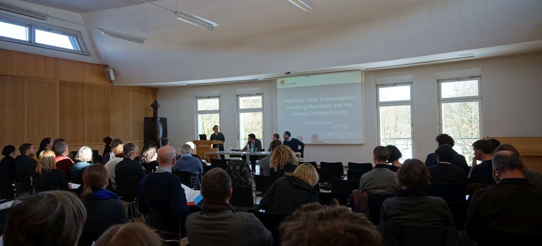 """Das Foto zeigt das Publikum und Votrgende der Konferenz """"Confronting the Colonial Past!"""" in den Räumen der Universität Hamburg."""