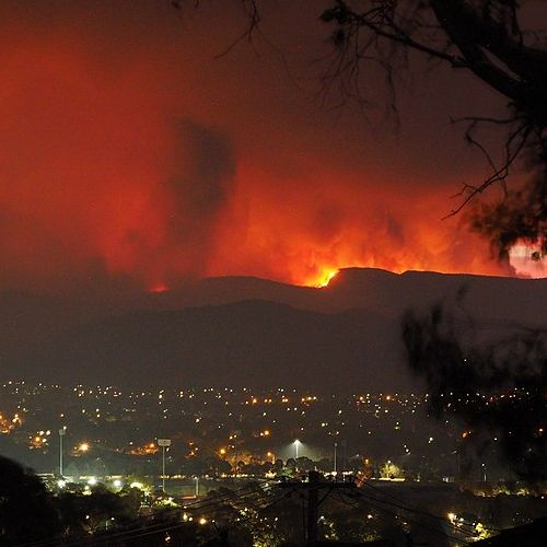 Zu sehen ist ein Feuer im Orroral Valley. Im Vordergrund sind die Lichter einer Stadt zu sehen.