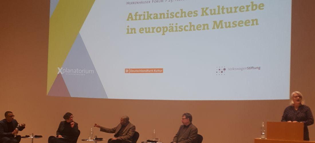 """Das Foto zeigt die Podiumsdiskussion. Die Teilnehmer der Diskussion sitzen auf einer Bühne über ihnen wird eine Präsentation n die Wand mit einem Beamer geworfen. Die gezeigte Folie trägt die Aufschrift """"Afrikanisches Kulturerbe in europäischen Museen""""."""