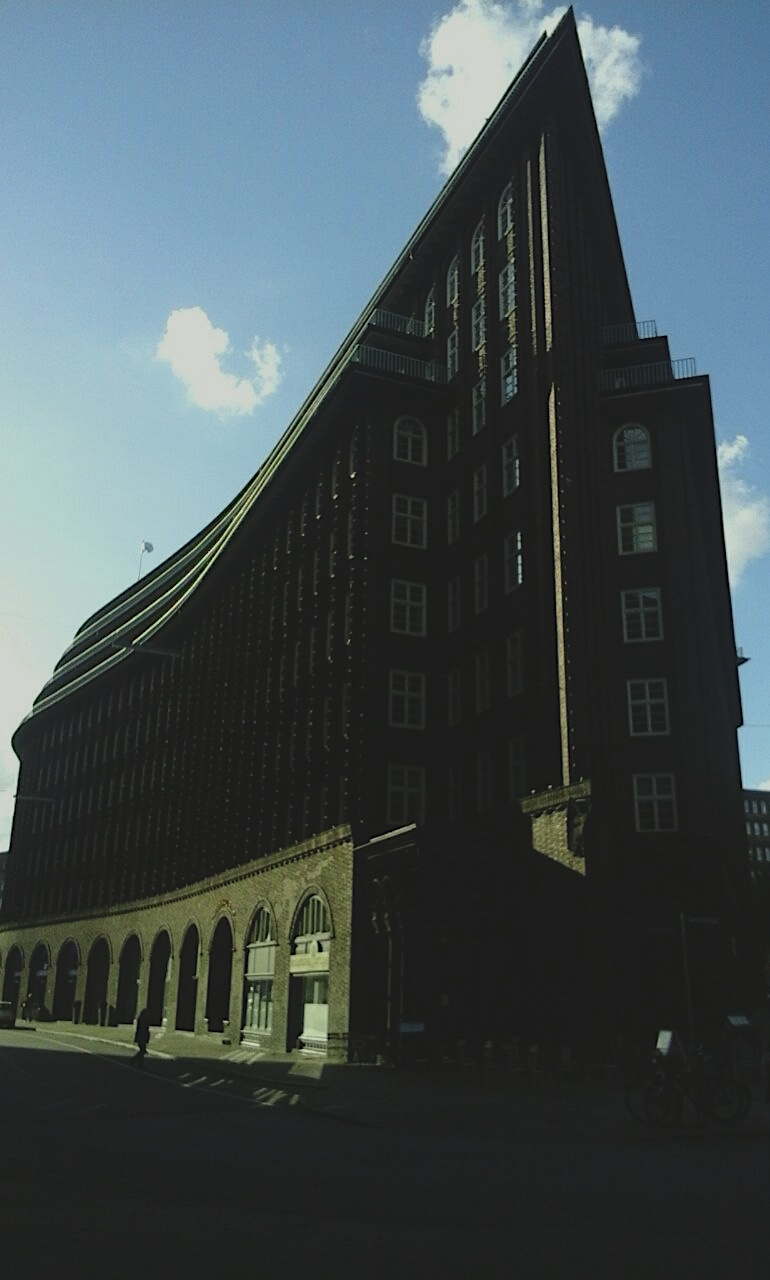 Das Foto zeigt das Schulhaus. Es ist ein dunkles Backsteingebäude zu sehen, das sich zum Betrachter hin zu einer Spitze verjüngt.