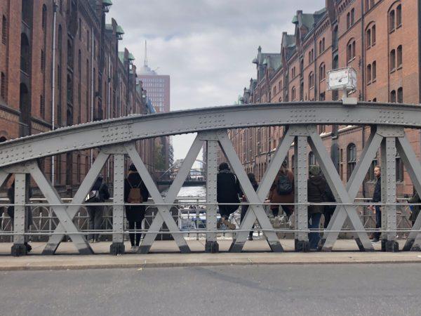 Das Foto zeigt den Blick von einer Straße/Brücke auf die Speicherstadt. Zwischen roten Backsteinfassaden ist ein Kanal zu sehen. Auf der Brücke stehen hinter einer Metallkonstruktion der Brücke mehrere menschen, die auf den Kanal blicken.