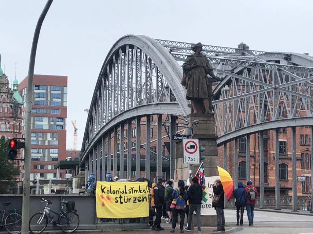 """Das Foto zeigt die Kolumbusstatue in der Speicherstadt. Die Statue aus Stein zeigt einen Mann auf einem Sockel und befindet sich an einer Brücke. Um die Statue steht eine Menschenmenge, es ist ein Banner mit der Aufschrift: """"Kolonialsymbol[e] stürzen"""" zu sehen."""