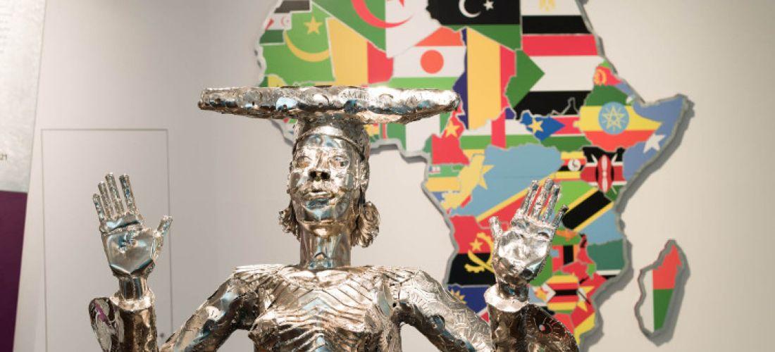 """Das Foto zeigt die Skulptur """"Looking for Grace"""" von Sokari Douglas Camp. Im Vordergrund ist eine Frau aus silbernen Metall zu sehen, die die Hände in die Höhe hebt. Im Hintergrund ist der afrikanische Kontinent mit den Flaggen aderafrikanischen Ländern in ihren jeweiligen Staatsgrenzen zu sehen."""