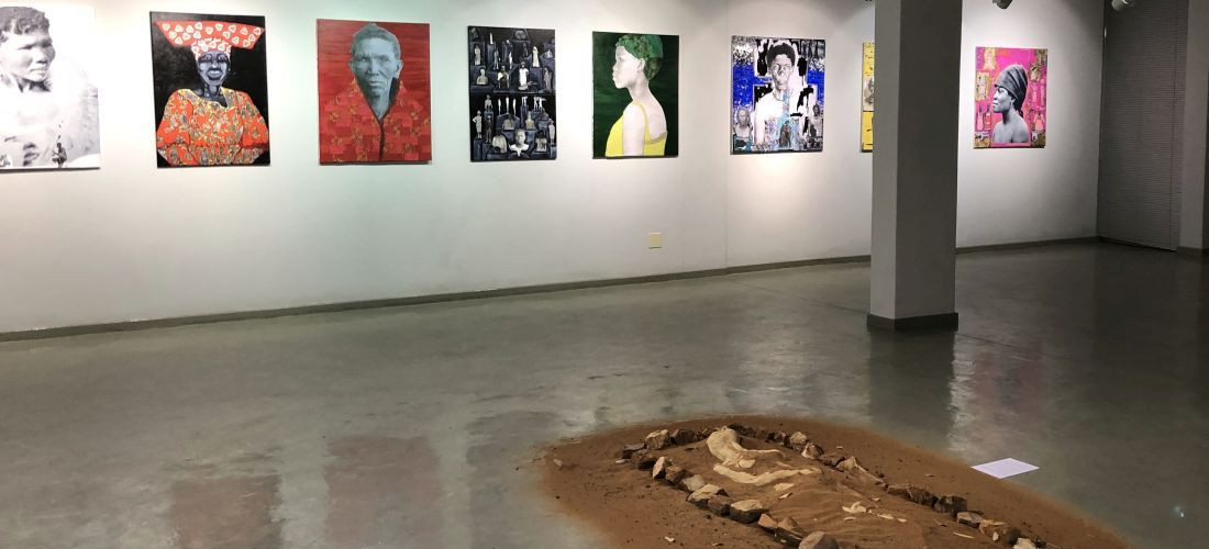 Das Foto zeigt einen Ausstellungsraum der Ausstellung 'Oviziere-Somgu: From Where Do We Speak?'. Das Foto zeigt eine Installation im Raum und acht Leinwände mit Porträtdarstellungen an einer Wand.