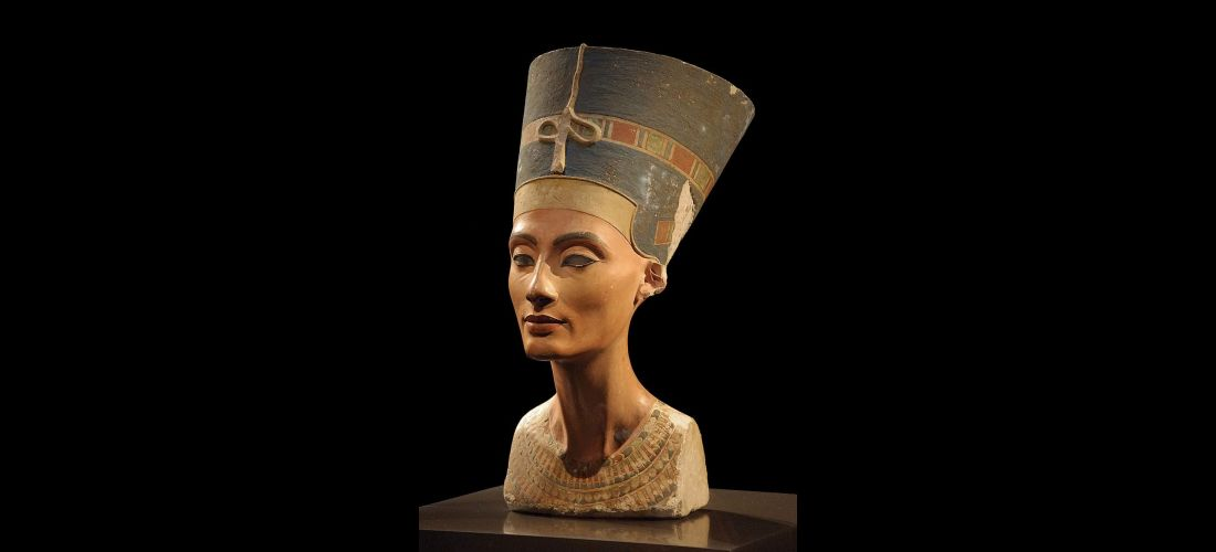 Fotografie der Büste der Nofretete, die sich im Neuen Museum in Berlin befindet. Nofretete wird in dieser Büste mit einer blauen Krone mit einem bunten Band und goldenem Stirnband präsentiert.