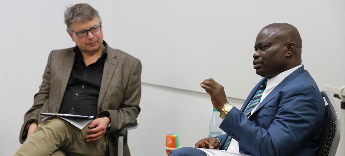 Das Foto zeigt Prof. Dr. Jürgen Zimmerer und Prof. Dr. Osarhieme Benson Osadolor in der Forschungsstelle während der Diskussion.