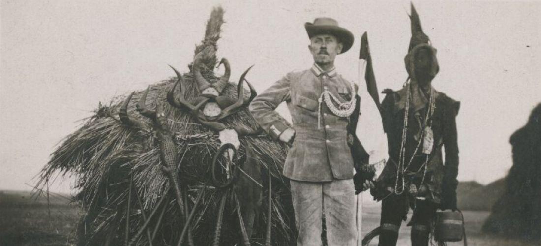Der historische Schwartz-Weiß-Silbergelatine-Abzug zeigt einen deutschen Soldaten in Uniform, einen Herero, und mehrere Objekte.