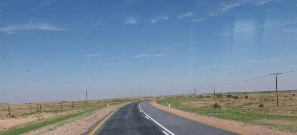 Das Foto zeigt eine Straße. Auf beiden Seiten der Straße erstrecken sich weite Flächen.