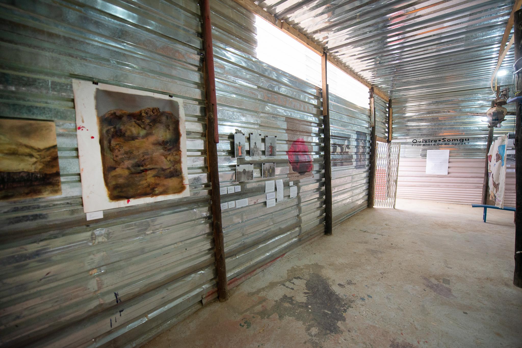 Impressionen aus der Ausstellung Ovizire • Somgu From Where Do We Speak. Ein metallverkleideter Ausstellungsraum mit diversen klein- und großformatigen Gemälden und Fotografien. Foto © StArtArtGallery