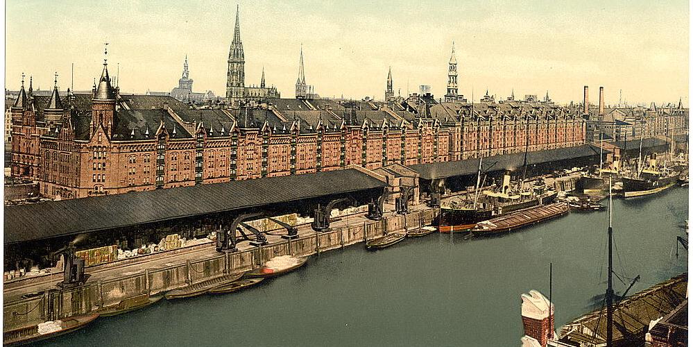 Das Bild zeigt eine historische Aufnahme in Farbe des Hamburger Freihafens und der Speicherstadt..