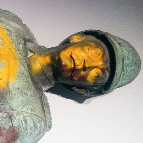 Das Foto zeigt den Kopf der liegende Wissmann-Statue, der mit gelber Farbe angesprayed wurde. Die Statue präsentiert Wissman in militärischer Uniform.