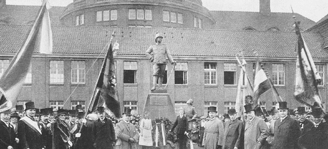 Das historische Schwarz-Weiß-Foto zeigt eine Feier von kolonialrevisionistischen Vereinen vor dem Wissmann-Denkmal um 1922. Mehrere der Teilnehmer schwenken Flaggen.
