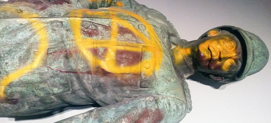 Das Foto zeigt die liegende Wissmann-Statue, die mit gelber Farbe angesprayed wurde. Die Statue präsentiert Wissman in militärischer Uniform.