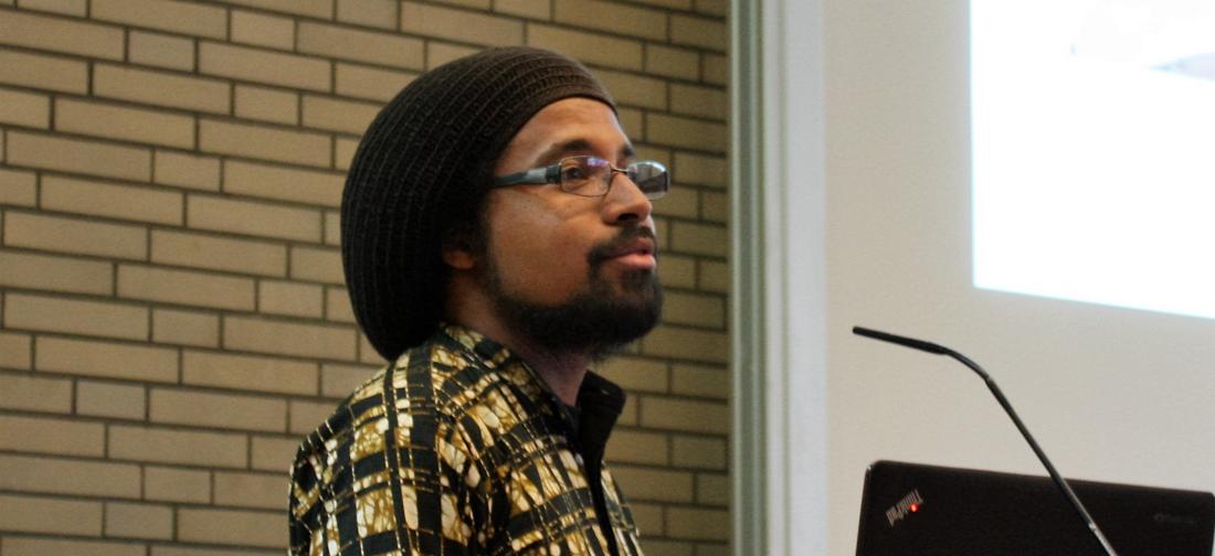 Das Foto zeigt Joshua Kwesi Aikins während seines Vortrags an der Universität Hamburg.
