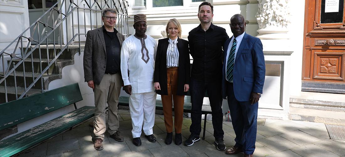 Gezeigt wird ein Gruppenfoto vor der Forschungsstelle von Prof. Dr. Jürgen Zimmerer, Idahosa Osagie Ojo, Isabel Eiser, Jonas Ehrsam, Prof. Dr. Osarhieme Benson Osadolor (von links nach rechts).