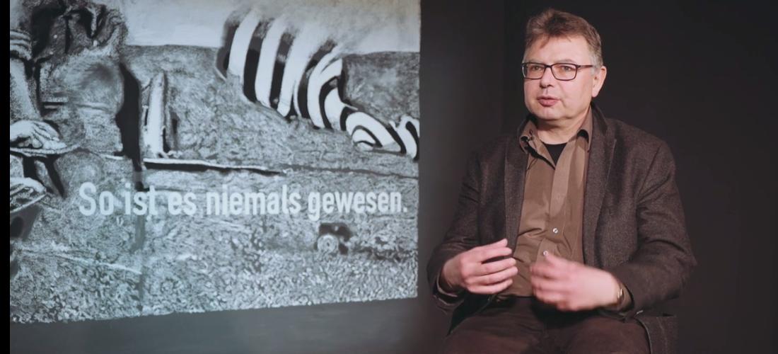 """Das Foto zeigt eine Aufnahme von Prof. Dr. Jürgen Zimmerer im Interview. Im Hintergrund is ein Bild mit der Aufschrift """"So ist es niemals gewesen""""."""