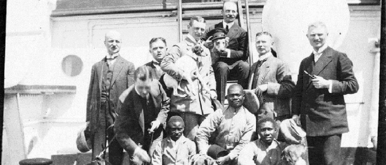 Die Schwartz-Weiß-Fotografie zeigt eine Gruppenaufnahme auf einem Schiff von drei Schwarzen Männern, sieben Europäern und fünf Hunden.