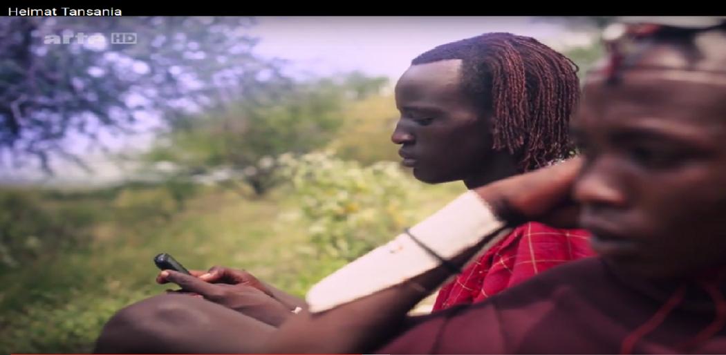 Filmszene: ein tansanischer Mann schaut auf sein Handy